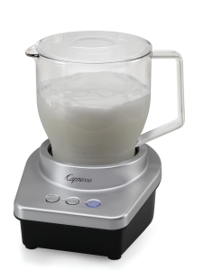 Front facing view of milk frother with clear colored pitcher of milk being frothed. Silver base of machine features three temperature options for frothing.