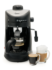 Front facing view of 4 cup espresso machine in black with silver panel on the lid featuring glass carafe. An espresso and cappuccino sit to the right of the machine.